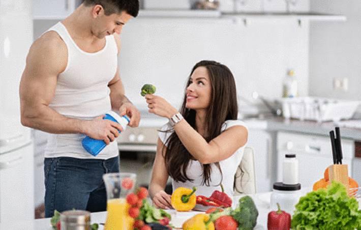 une femme au régime pour maigrir tend du brocoli à son homme