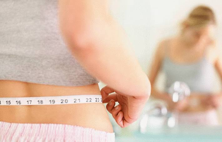 une femme devant son miroir mesure sa taille pour vérifier si elle a maigri