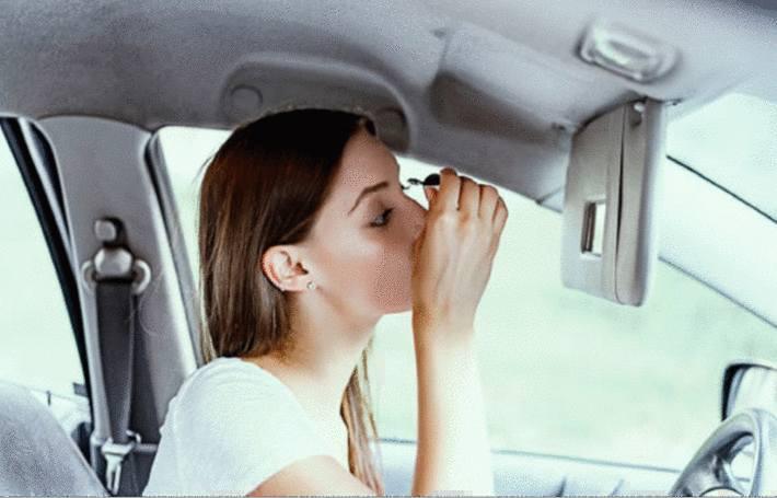 dans sa voiture une femme applique du mascara sur ses cils