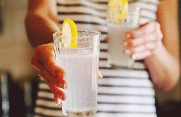 une femme tend un verre de jus de citron dans le cadre d'un régime minceur
