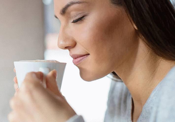une femme boit un café dans le but de maigrir