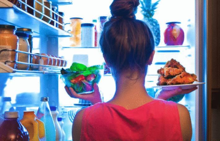 devant son frigo pour maigrir une femme héisite entre des légumes et de la viande