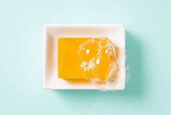 savon-jaune-formant-des-bulles-sur-porte-savon-blanc